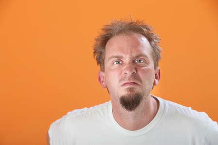 Frowning bearded Caucasian man on orange background photo