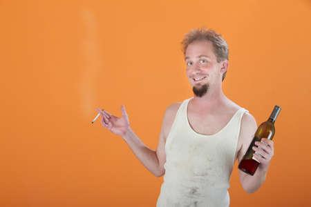 wifebeater: Felice caucasica uomo che tiene una bottiglia e una sigaretta  Archivio Fotografico