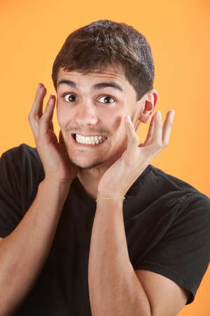 Uncontrollable joy for Latino teen on an orange background photo