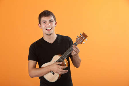 cool guy: Happy Native American teen playing a ukulel Stock Photo