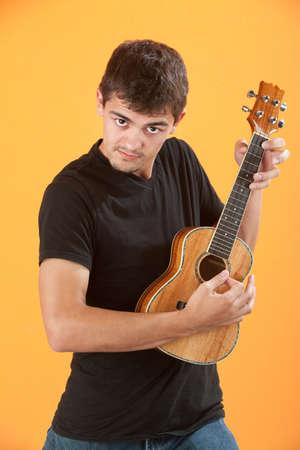 Serious Latino teen ukulele player on an orange background Stock Photo - 9136867