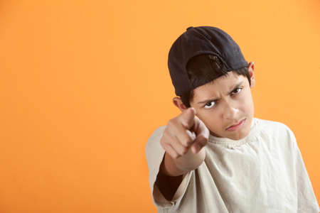 Serious or angry Latino kid points index finger