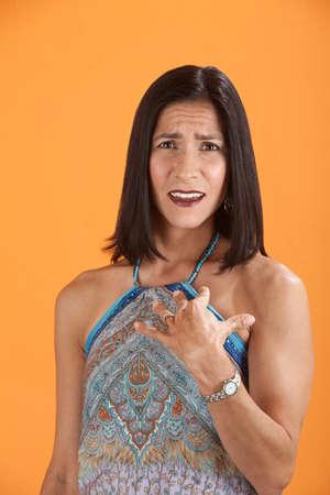 baffle: Young Latina on an orange background looks baffled