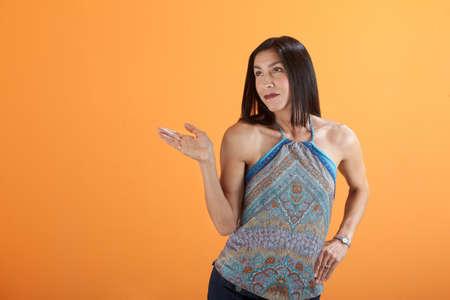 Hispanic woman holding or showing nothing on an orange background photo