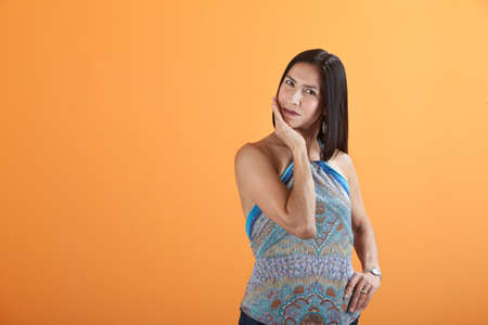 Young Mexican American woman on an orange background with palm on chin photo