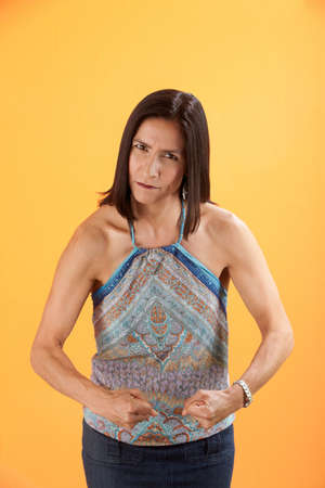 tough: Tough Latina woman on orange background shows off her muscles Stock Photo