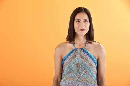 Confident young Latina woman on an orange background photo