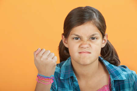 Angry Latina kid with clenched fist on an orange background