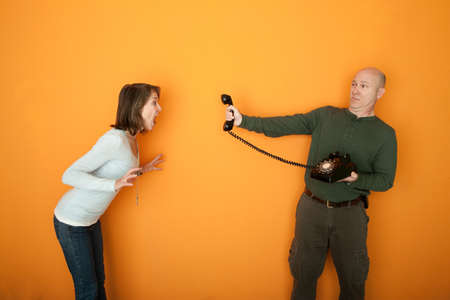 Man holds telephone while woman yells at it photo