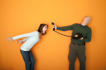 Man holds telephone while angry woman shouts into it photo
