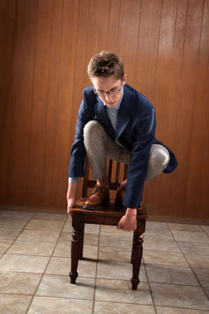 Young Caucasian man stands on a chair, looking down Stock Photo - 9136901