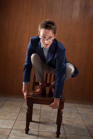 Odd young Caucasian man on wooden chair Stock Photo - 9136887