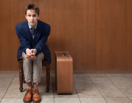 Serious young Caucasian traveller seated on chair Stock Photo - 9136881
