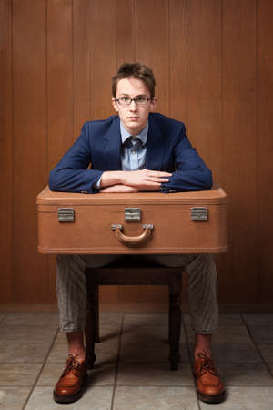 Serious Caucasian man sitting on chair with suitcase Stock Photo - 9136883
