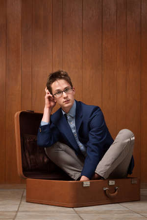 Thinking young Caucasian man sits inside a suitcase Stock Photo - 9136897