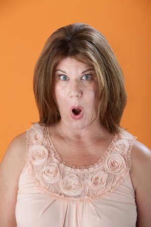 Shocked Caucasian woman on orange background