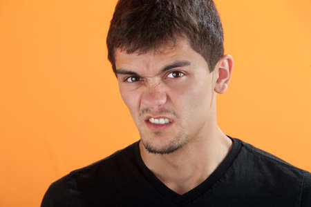 grinding teeth: Latino teen on orange background clenches his teeth