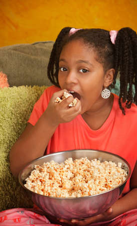 bowl of popcorn: Little African American girl in pajamas eats popcorn