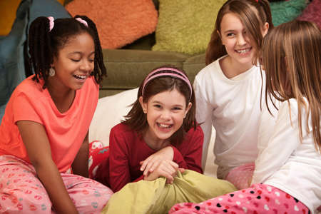 preteen girls: Group of four happy little girls at a sleepover Stock Photo