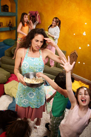 messy room: Misbehaving kids throwing popcorn with an unhappy babysitter Stock Photo