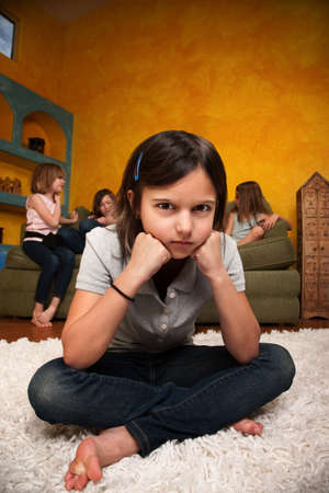 sleepover: Sad little girl sits away from her friends