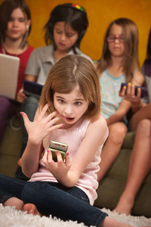 sleepover: Surprised little Caucasian girl with a handheld device