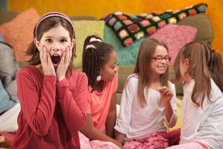 Shocked Little Caucasian girl with friends at a sleepover photo