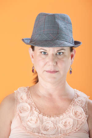 bbw: Serious Caucasian woman with hat on orange background