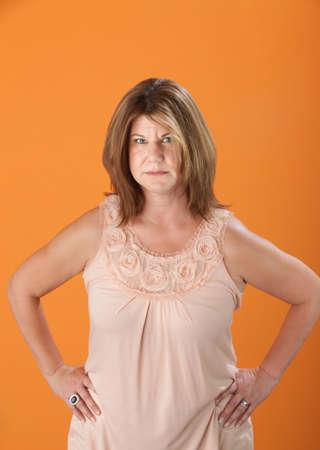 mujer enojada: Sospechosa mujer rubia cauc�sica sobre fondo naranja Foto de archivo