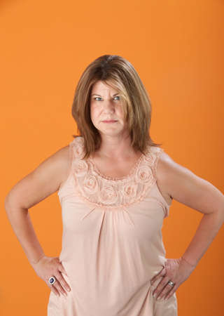 angry woman: Suspicious Caucasian blonde woman on orange background