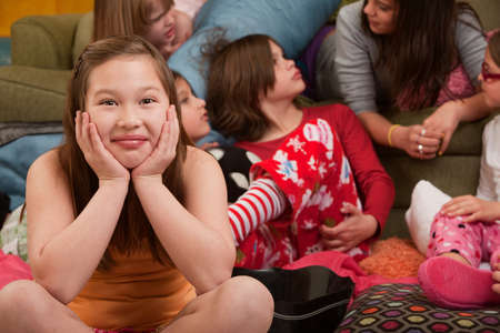 Happy girl with friends seated on floor at a sleepover Stock Photo - 9183667