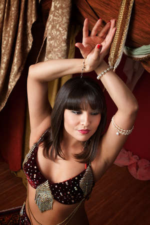 Gorgeous Arab belly dancer with hands crossed above her head photo