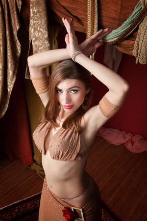 bellydancing: Gorgeous Arab belly dancer with hands raised