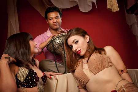 Two gorgeous belly dancers with handsome Indian dummer photo