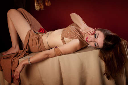 Beautiful Arab woman lying down with hand on face photo