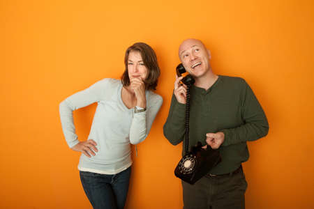 Middle aged Caucasian man on telephone while woman listens to the conversation Stock Photo - 9269962