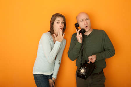 mischeif: Shocked Caucasian woman with hand on mouth listening to a telephone conversation