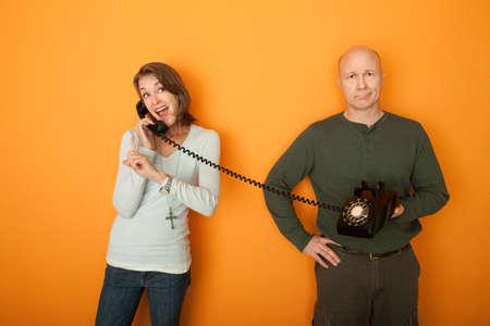bored man: Felice donna indoeuropeo sulla conversazione telefonica con uomo annoiato