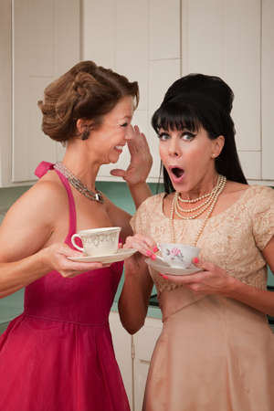 Pretty retro Caucasian women gossiping over coffee in kitchen