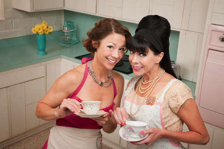 Two retro housewives with tea in a kitchen photo