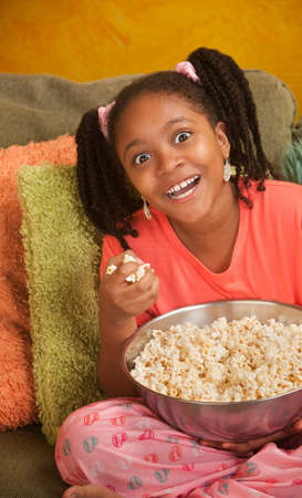 slob: Overjoyed little African American girl with a bowl of popcorn