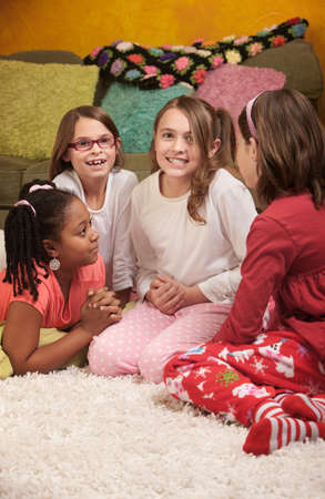 Little girl wrings hands with friends at a sleepover photo