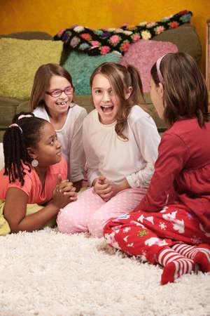 pijamada: Cuatro ni�as felices compartiendo historias en un dormitorio