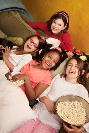 sleepover: Four happy little girls on a couch eat popcorn Stock Photo