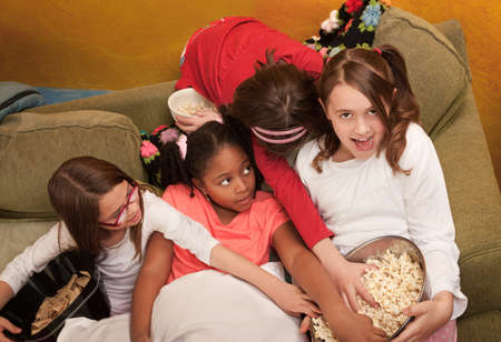 sleepover: Little girls grab popcorn at a sleepover