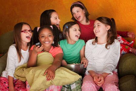 pijama: Grupo de ni�as viendo televisi�n comiendo palomitas de ma�z Foto de archivo