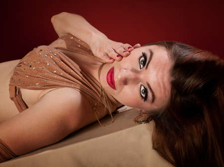 Attractive Arab belly dancer lying down on maroon background photo