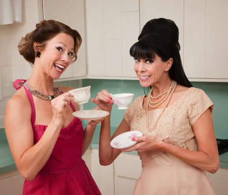 fake smile: Two retro style women enjoying tea or coffee in the kitchen Stock Photo