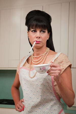 Tough housewife in apron with cigarette and coffee cup