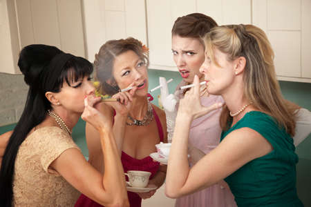 Unsure young woman around older ladies smoking in the kitchen
